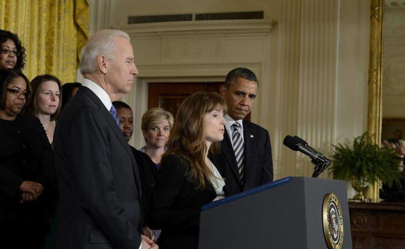 Barack Obama (d) y el vicepresidente Joe Biden (i) escuchan a la defensora del control de armas, Katerina Rodgaard (c) en rueda de prensa. (EFE)