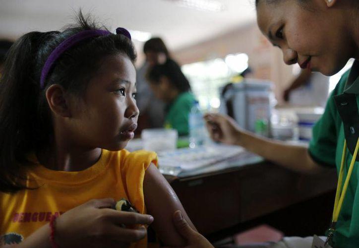 Una estudiante filipina espera a que una enfermera le ponga la vacuna contra el dengue. (Archivo/EFE)