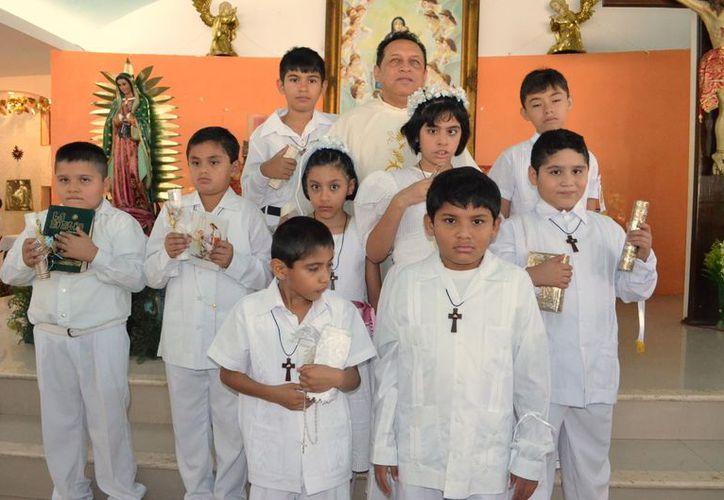 El padre Miguel José Medina Oramas acompañado de los neocomulgantes. (Theany Ruz/SIPSE)