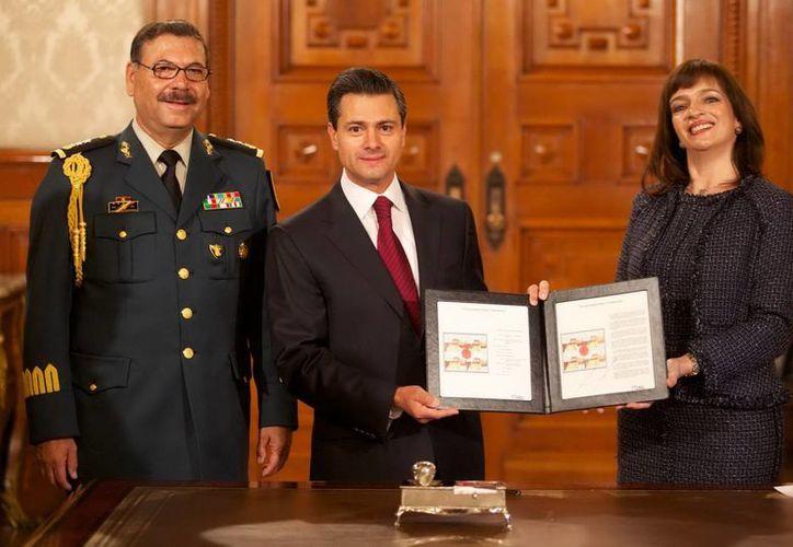 Peña Nieto aparece junto con la directora general del Servicio Postal Mexicano, Yuriria Mascott Pérez. (Notimex)