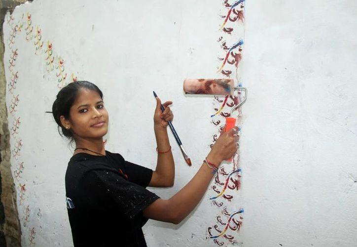 Arte precolombino transforma el gris de la pobreza en un colorido barrio, en India. (EFE)