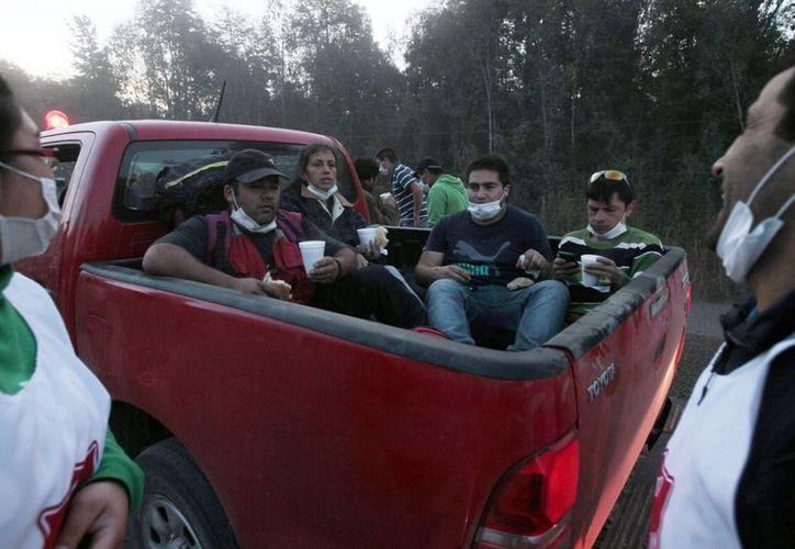 Imagen de un grupo de personas son evacuados de la ciudad de Ensenada , destruido por las cenizas de la erupción del volcán Calbuco en Puerto Varas, Chile. (AP/ Luis Hidalgo)