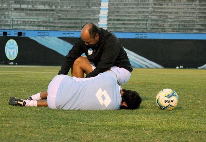 El médico del CF Merida, Miguel Ángel Nazul Aké Montiel, atiende a uno de los astados. (Milenio Novedades)