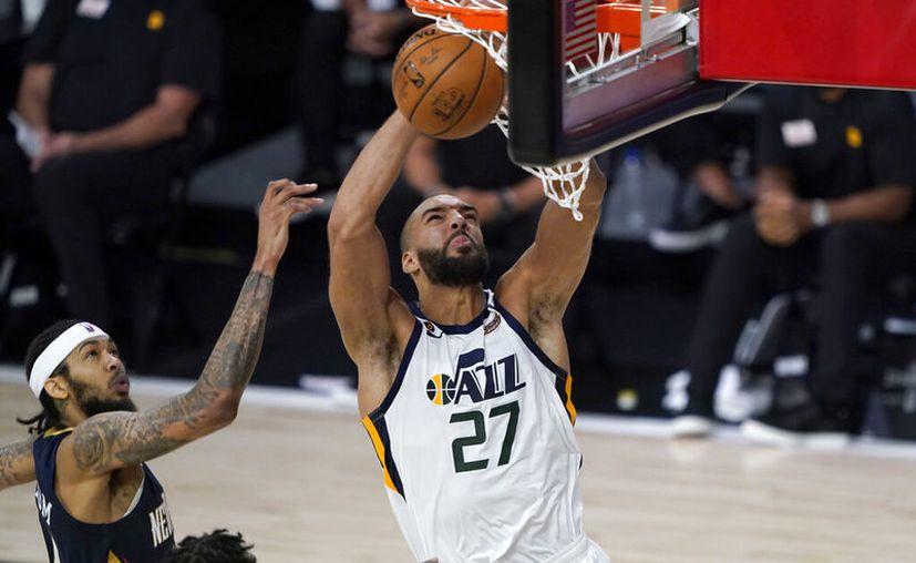 Rudy Gobert encesta para el Jazz ante la mirada de Brandon Ingram, en el juego que marcó la reanudación de la NBA, suspendida desde el 11 de marzo por el Covid-19. (Foto: AP)