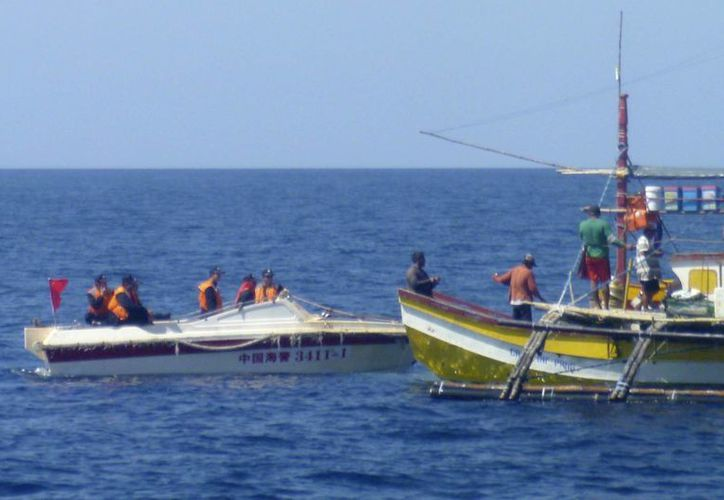Un patrullero chino se acerca al pesquero del filipino Renato Etac cerca de los arrecifes de Scarborough Shoal en el Mar del Sur de China el 27 de febrero del 2015. En más de una ocasión guardias chinos le apuntaron sus rifles, pero Etac dice que sabe que no dispararán porque ello podría generar una guerra. (AP Photo/Renato Etac)