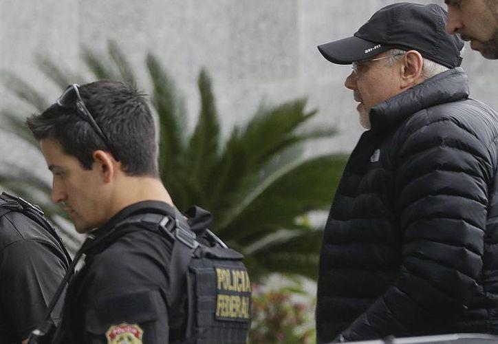 El ex ministro de Finanzas de Brasil Guido Mantega es escoltado por agentes de la Policía Federal al llegar a la sede de la fuerza policiaca en Sao Paulo, Brasil. (AP/Andre Penner)