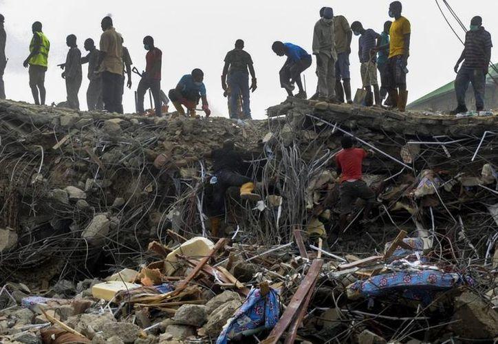 Miembros de diferentes equipos de rescate de Nigeria inspeccionan los escombros de una iglesia derruida en Lagos, Nigeria. (EFE/Archivo)