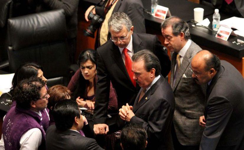 Senadores de las izquierdas y del PRI, dialogando durante la sesión de hoy. (Notimex)