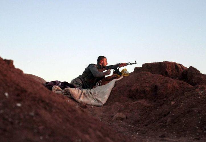 Un soldado de las Unidades de Protección del Pueblo Kurdo vigila la localidad de Alouk, a unos cuatro kilómetros de Ras Al-Ayn en Siria. (EFE)