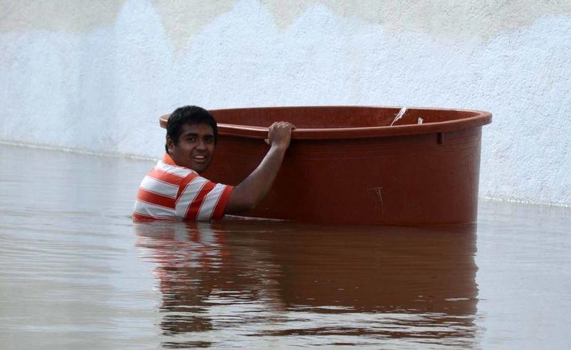En Tixtla, Guerrero, cientos de personas fueron evacuadas luego de que sus viviendas quedaron totalmente inundadas por el desbordamiento de la Laguna Negra. (Notimex)