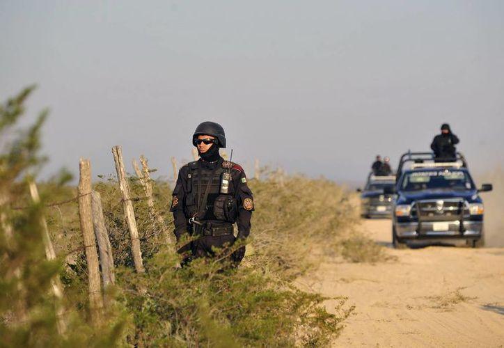 Militares y policías patrullan el sitio donde fueron hallados cadáveres en Mina, Nuevo León y que, se presume, pertenecen a músicos de la banda Kombo Kolombia. (EFE)