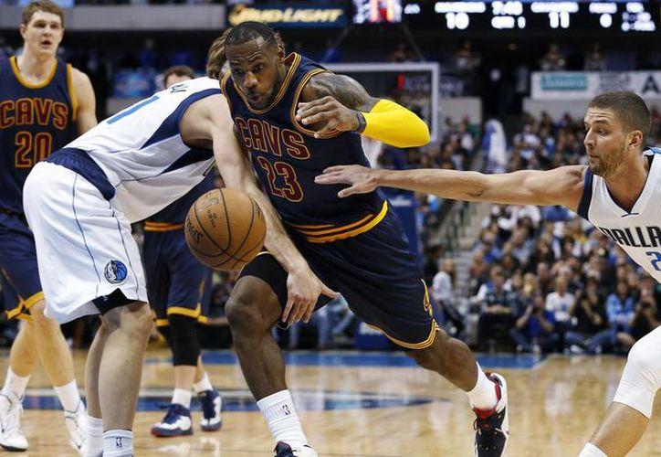 LeBron James se abre paso entre Dirk Nowitzki (i) y Chandler Parsons (25) en partido que ganaron Cavaliers de Cleveland a Mavericks de Dallas y en el que James impuso una nueva marca de asistencias en el seno de Cavs. (Foto: AP)