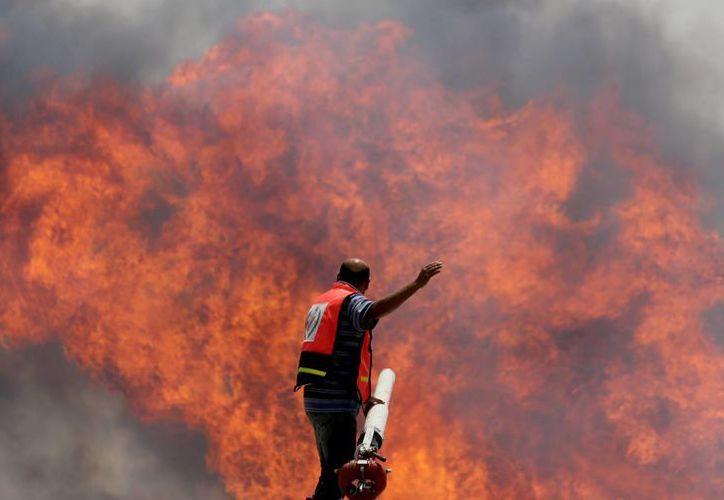 Bomberos palestinos combaten las llamas en una terminal de cargas en el cruce Karni entre Gaza e Israel alcanzada por fuego de tanques israelíes. (Agencias)