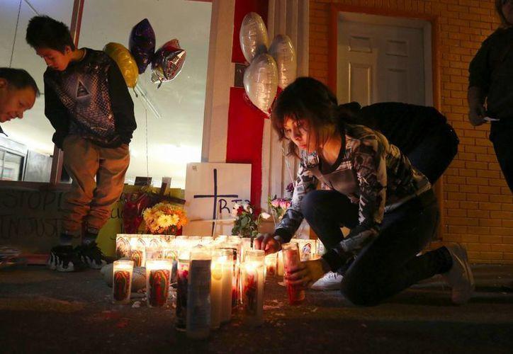 Un grupo de personas coloca velas en el lugar donde falleció el mexicano Antonio Zambrano Montes a manos de un policía estadounidense en febrero pasado. Arizona y Oklahoma son los estados donde agentes de la policía balean a los sospechosos. (Archivo/AP)