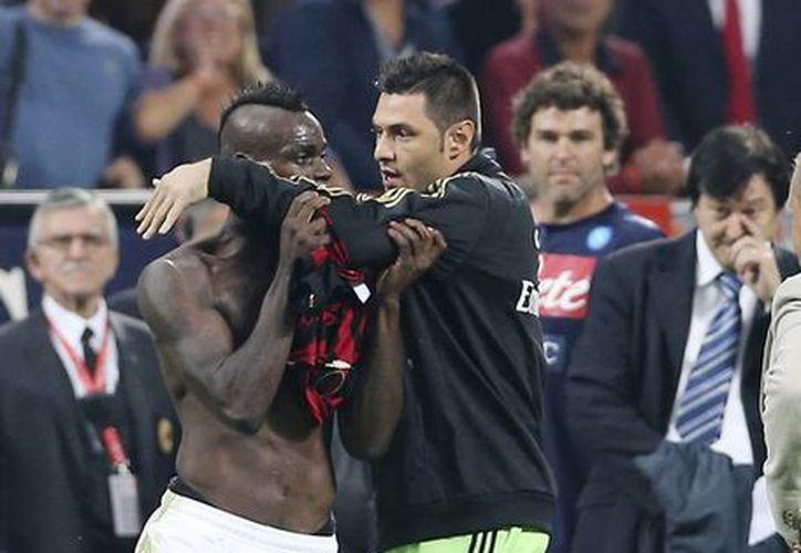El delantero del Milan Mario Balotelli (i) es contenido por Marco Amelia, tras ser expulsado en el partido contra el Napoli. (Agencias)