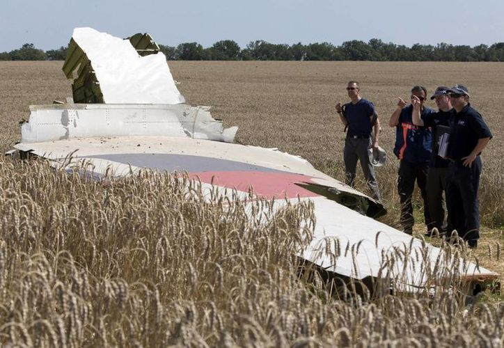 Investigadores examinan los restos del avión comercial de Malaysia Airlines caído en Ucrania el 17 de julio del año en curso. La foto corresponde al 1 de agosto. (Foto: AP)
