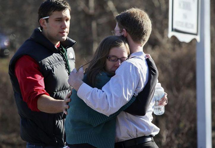 Unas personas se consuelan mutuamente en el exterior de la escuela Sandy Hook en Newtown, después del tiroteo. (EFE)