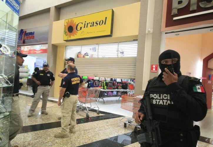 Agentes federales y estatales durante el operativo conjunto en las plazas comerciales. (Jorge Sosa/SIPSE)