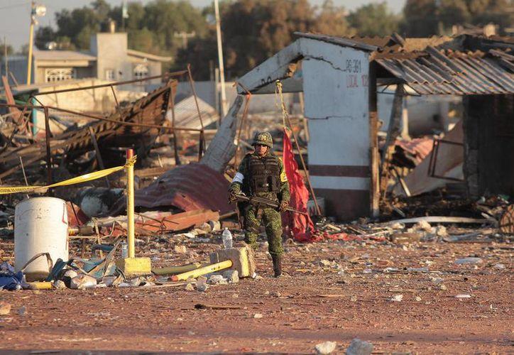La explosión destruyó la mayoría de los puestos que había en el mercado de San Pablito. Imagen de un soldado resguardando la zona donde ocurrió el incidente. (Notimex)