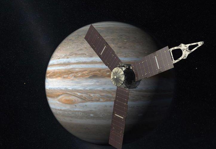 En esta interpretación artística creada por la NASA y JPL-Caltech se ve la nave espacial Juno mientras sobrevuela Júpiter. Juno entrará a la órbita del gigantesco planeta de gas este lunes, cinco años después de su lanzamiento. (AP)