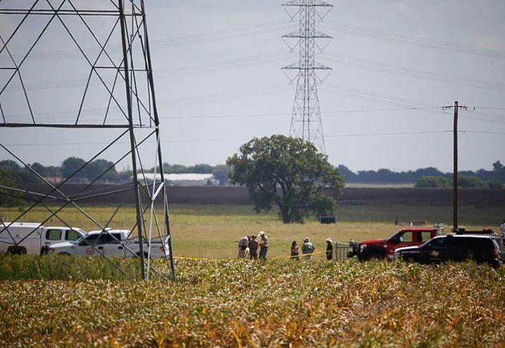 Investigadores trabajan en un campo agrícola cerca de Lockhart, Texas, donde un globo aerostático se desplomó matando a por lo menos 16 personas que iban a bordo. (Ralph Barrera/Austin American-Statesman via AP)