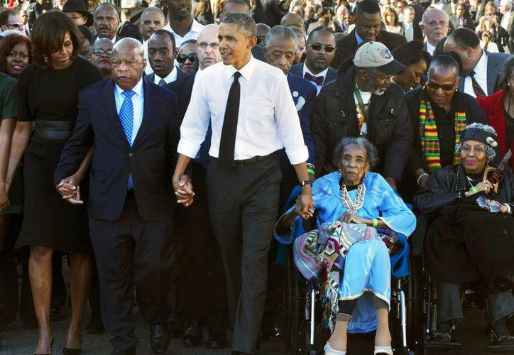 Imagen de archivo del presidente de EU, Barack Obama, al sostener la mano del epresentante demócrata de Georgia, John Lewis (izq), y de la activista Amelia Boynton Robinson durante el 50 aniversario del 'Domingo Sangriento'. (Agencias)