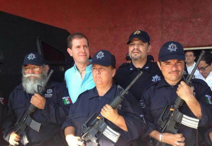 El vocero general de autodefensas, Estanislao Beltrán (i) con el comisionado de Seguridad estatal, Alfredo Castillo, durante la integración de la nueva Fuerza Rural Estatal de Michoacán. (Notimex)