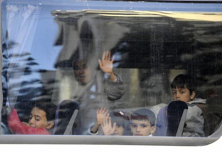 Varios refugiados sirios saludan desde un autobús en la sede de la Organización Mundial para las Migraciones (OIM) de Beirut (Líbano) antes de subir a un avión con rumbo a Alemania la semana pasada. (EFE)