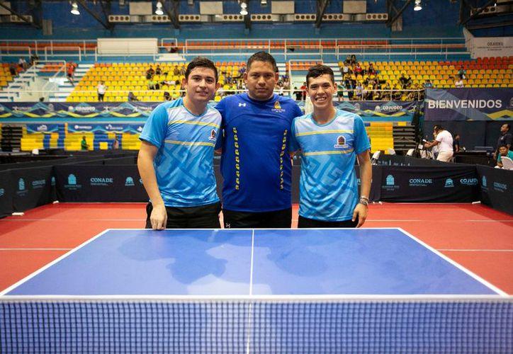 Mauricio Cayetano y Darío Arce, integrantes de la categoría Sub 18 Varonil, en la modalidad de dobles, posan en compañía de su entrenador Ricardo Sosa. (Ángel Villegas/SIPSE)