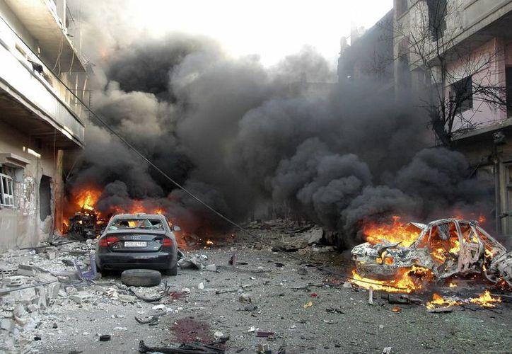 Vista general de las llamas y el humo que provienen de los dos coches bomba que acaban de estallar en la calle al-Khodhary en Homs. (EFE)