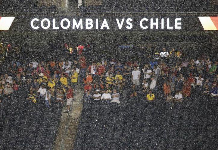 Los espectadores del partido entre Chile y Colombia de la Copa América Centenario soportan un torrencial aguacero en el Soldier Field de Chicago. (Agencias)