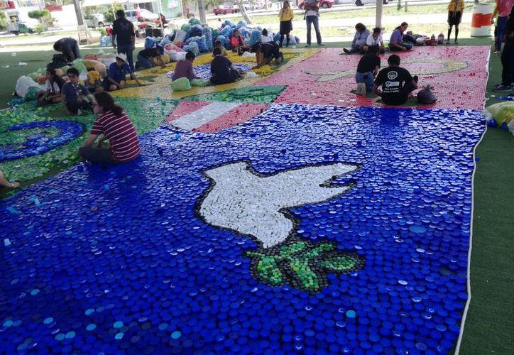 Con las tapas los participantes formaron varias mosaicos con figuras como la bandera yucateca. (Milenio Novedades)
