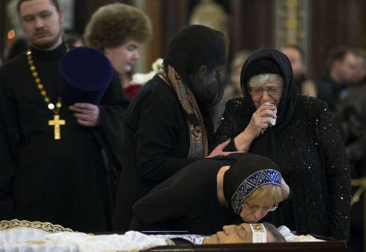 Marina, viuda de Andrei Karlov, lo besa en la frente mientras su suegra la observa con lágrimas en los ojos. (AP/Alexander Zemlianichenko)