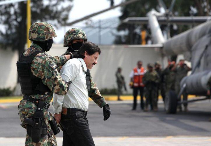 Guzmán Loera en su camino a ser trasladado en un helicóptero de la Policía Federal al penal de Almoloya de Juárez el 22 de febrero, poco después de su arresto en Mazatlán. (Agencias)
