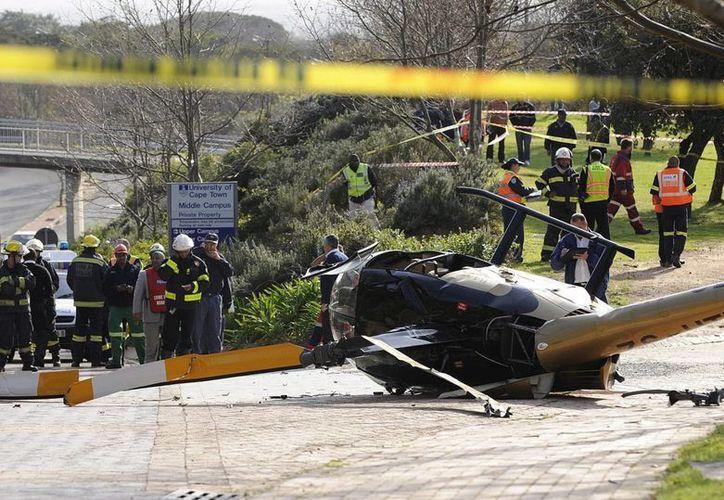 Un inspector de las autoridades de aviación sudafricanas analiza los restos de un helicóptero que se ha estrellado en Sudáfrica. (EFE)