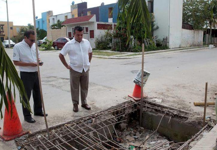 El presidente municipal supervisa los trabajos de reparación en las rejillas, en respuesta a las peticiones que le hacen los vecinos. (Redacción/SIPSE)