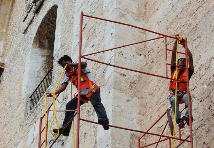 Personal de las empresas privadas trabaja en la fachada del templo mayor del centro de Mérida. (Milenio Novedades)