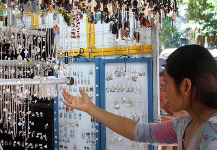 En general, el turismo busca la  artesanía local para llevarse de recuerdo. Imagen de una mujer en un local de bisutería de plata, en el centro de Mérida. (Milenio Novedades)