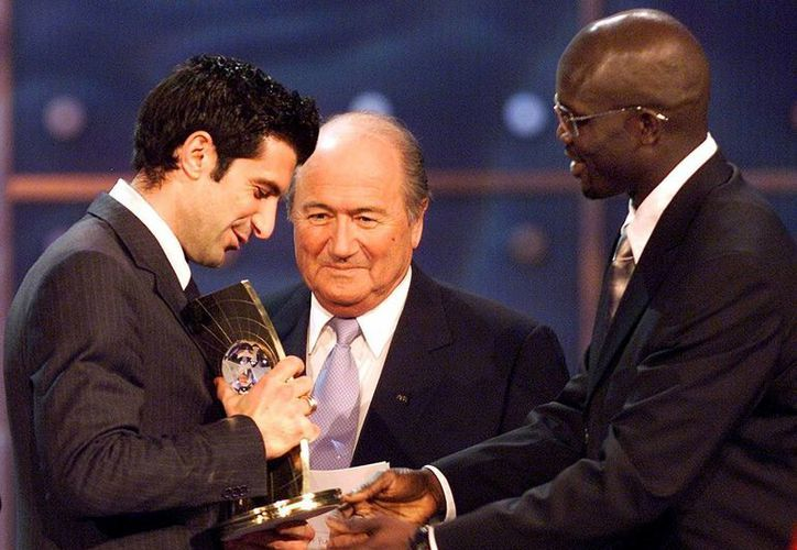 Luis Figo (i), quien en esta foto de 2001 recibe el Balón de Oro, tratará de desbancar a Josep Blatter (c), quien lidera esa organización desde 1998. (Foto: AP)