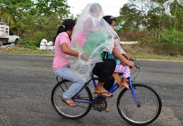 Pese a que este domingo sólo cayó una llovizna en Mérida, algunas personas optaron por protegerse. (Luis Pérez/SIPSE)