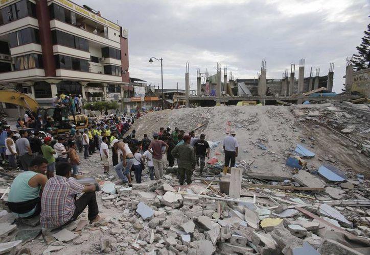 Numerosos hombres observan un edificio derrumbado en Pedernales, Ecuador. Socorristas sacaron  de este lugar a sobrevivientes de los escombros. (Foto AP / Dolores Ochoa)
