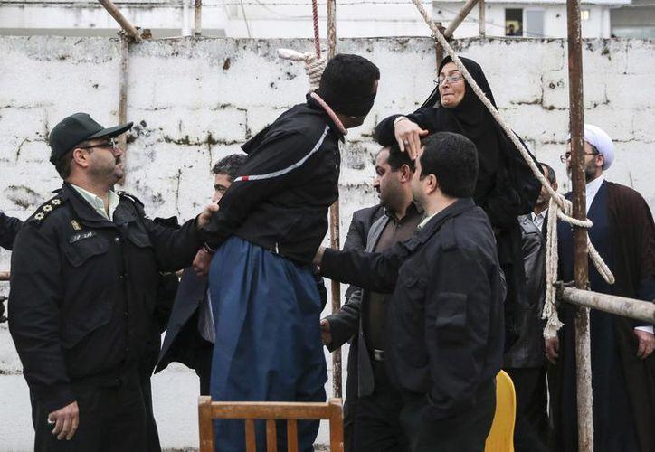 En el último minuto, cuando el inculpado estaba por ser ahorcado, la madre de Hosseinzadeh (d) abofeteó y perdonó al asesino de su hijo. (AP)