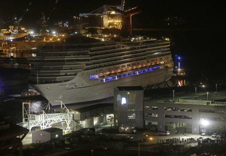 El crucero Triumph, de la compañía Carnival, es remolcado hacia el atracadero en Mobile, Alabama. (Agencias)