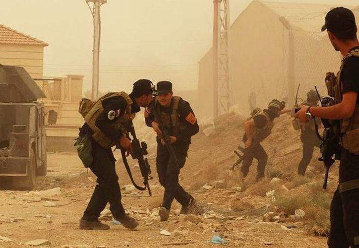 Soldados iraquíes se defienden de un ataque del grupo extremista Estado Islámico, durante una tormenta de arena en Ramadi, Irak. (AP Foto)