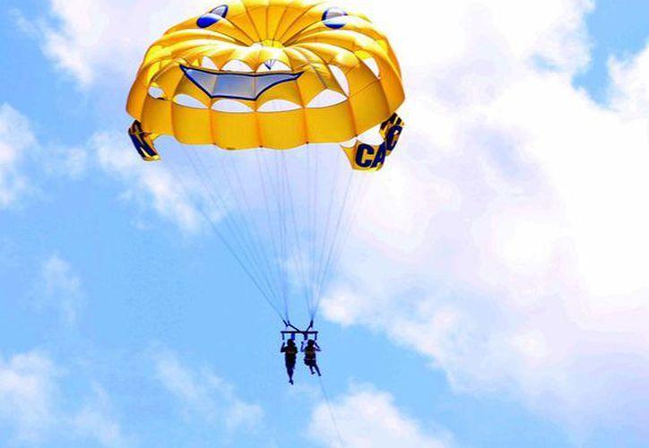 Los turistas aprovechan ver el paisaje que ofrecen las playas de Cancún desde el parachute. (Israel Leal/SIPSE)