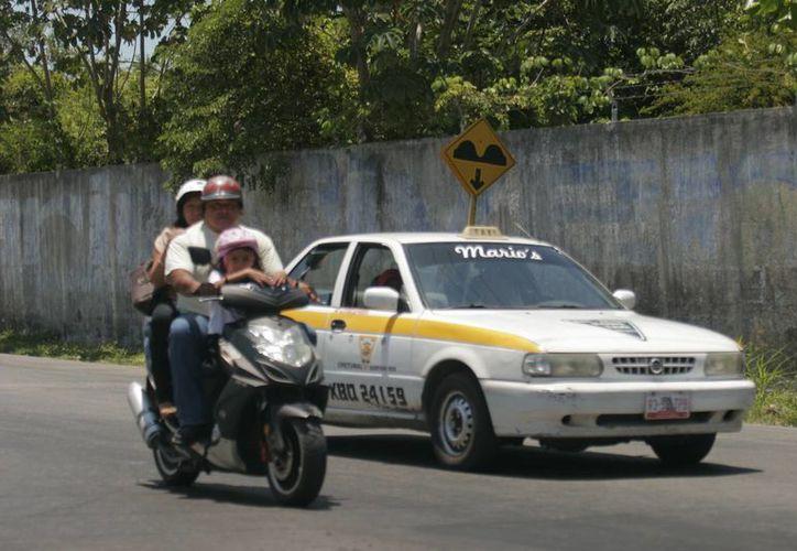 Los menores que sean transportados en motocicleta, se les debe de colocar el casco y no viajar más de dos personas. (Harold Alcocer/SIPSE)