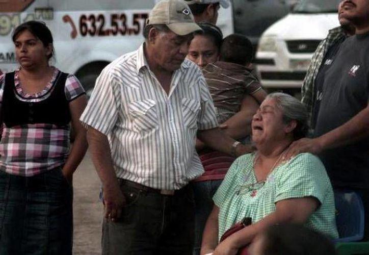 Una mujer espera el rescate del cuerpo de un familiar fuera de la mina Pasta de Conchos, en 2006. (Archivo/Notimex)