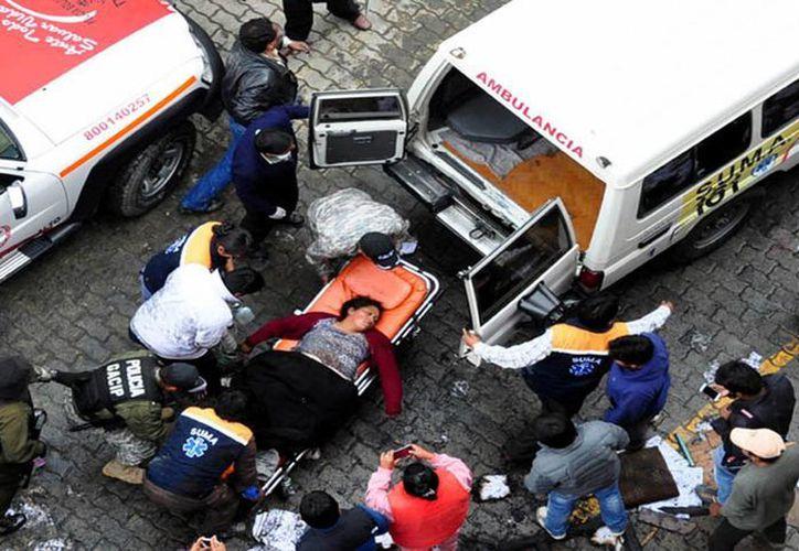 Policías y rescatistas transportan a una mujer herida tras un incendio provocado por manifestantes este miércoles 17 de febrero en El Alto, Bolivia. (EFE)