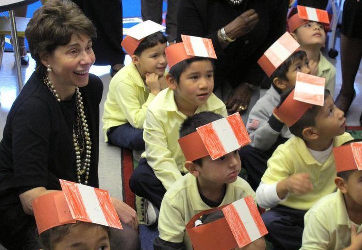 Imagen de la coordinadora de la junta escolar del estado de Nueva York Merryl Tisch (izquierda), mientras asiste a una clase bilingüe con niños de preprimaria en la escuela Washington-Rose en Roosevelt, Nueva York. (Foto AP/Frank Eltman, Archivo)