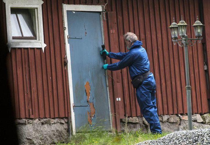 Un oficial de la policía forense trabaja en una propiedad afuera de Knislinge, donde un hombre mantuvo cautiva a una mujer durante una semana. (Agencias)